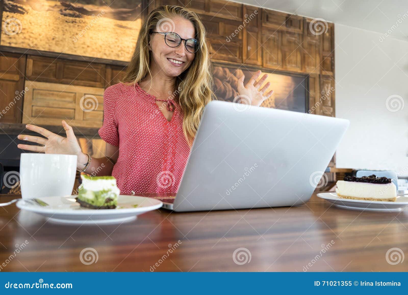 Το νέο κορίτσι εργάζεται στον υπολογιστή και το κέικ, τρόφιμα στον υπολογιστή, μια κακή συνήθεια τρώει