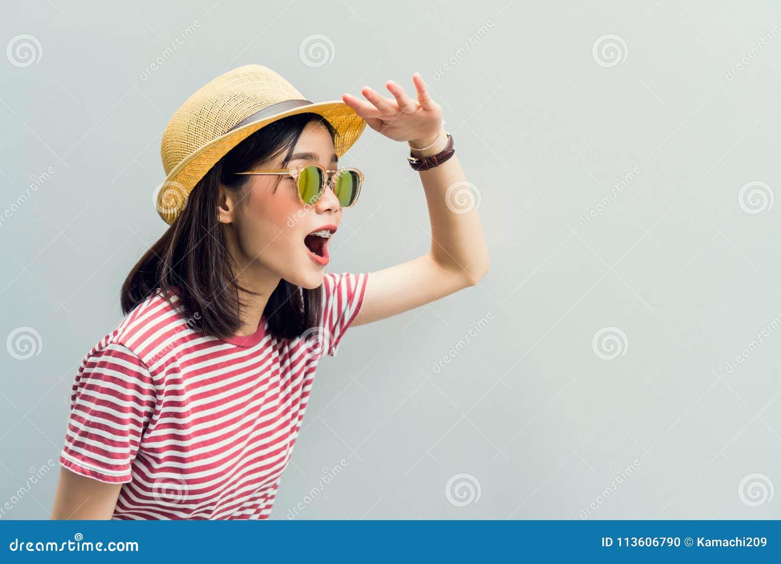 Το νέο κορίτσι ευτυχές ανυπομονεί να βρεί κάτι Γυαλιά ηλίου ένδυσης με μια αντανάκλαση της ελαφριάς ηλιοφάνειας