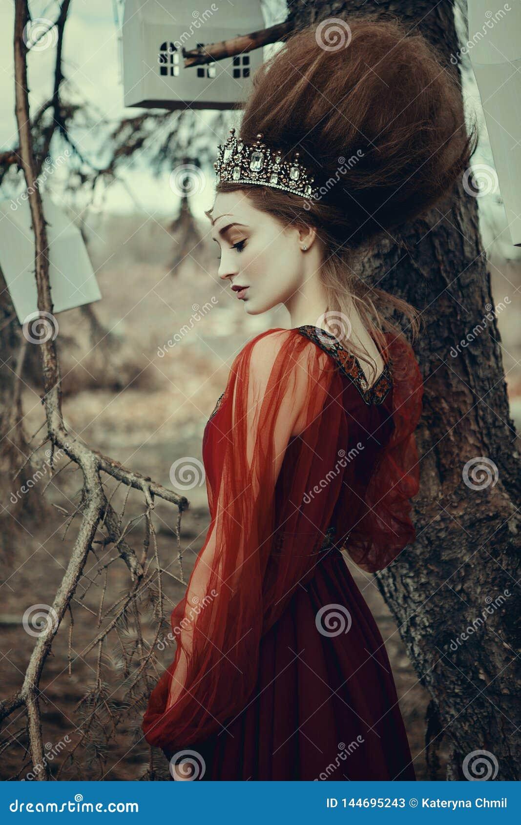 Το νέο κορίτσι θέτει σε ένα κόκκινο φόρεμα με το δημιουργικό hairstyle