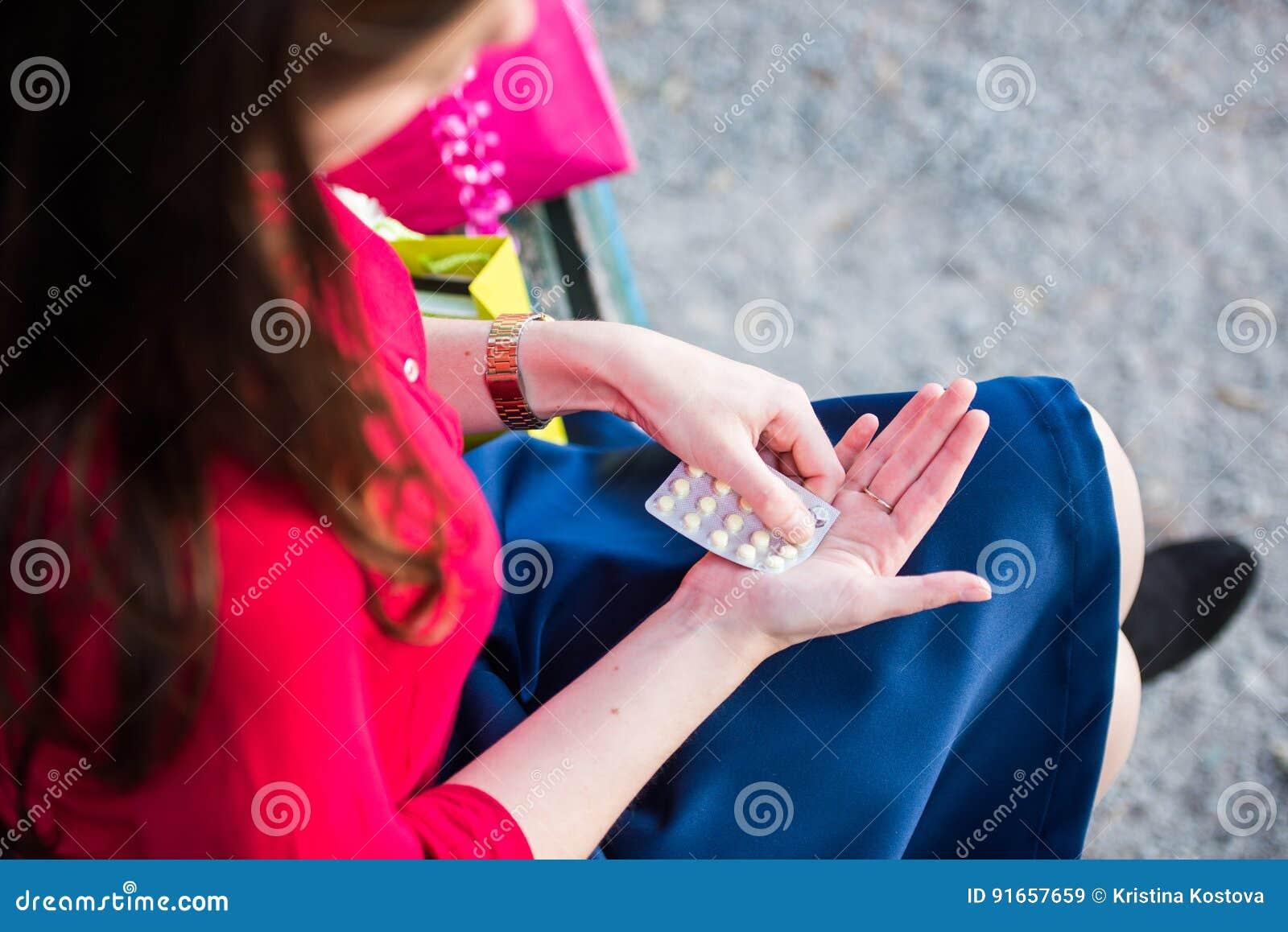 Το νέο κορίτσι παίρνει ένα χάπι στο πάρκο