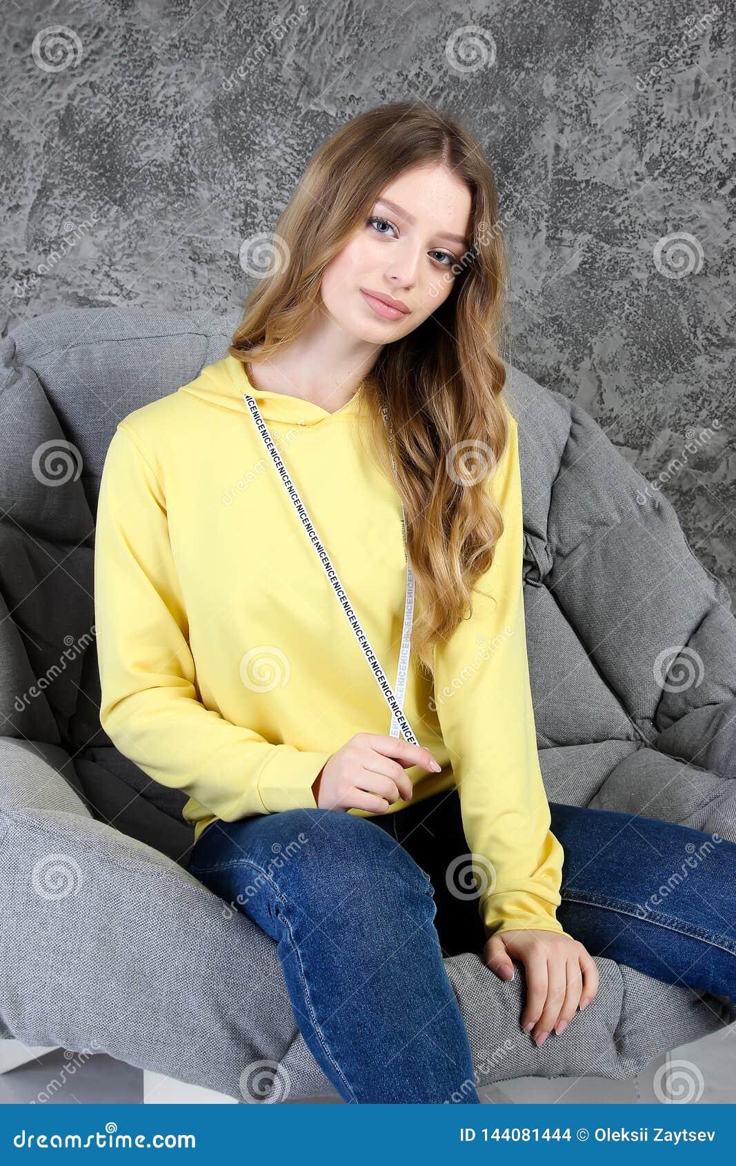 Το νέο κορίτσι σε μια φόρμα γυμναστικής κάθεται σε ένα μοντέρνο εσωτερικό