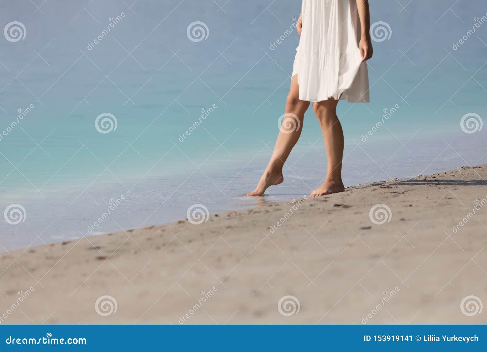 Το νέο κορίτσι στέκεται χωρίς παπούτσια στην άμμο