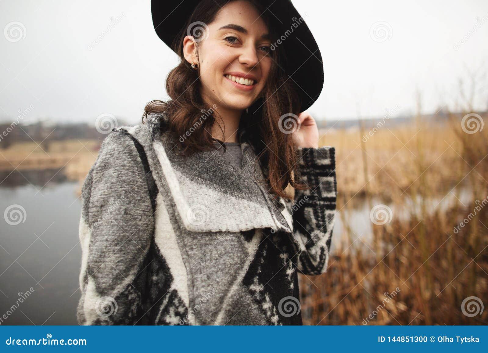 Το νέο κορίτσι στην γκρίζα ζακέτα και το μαύρο καπέλο χαμογελά και θέτ