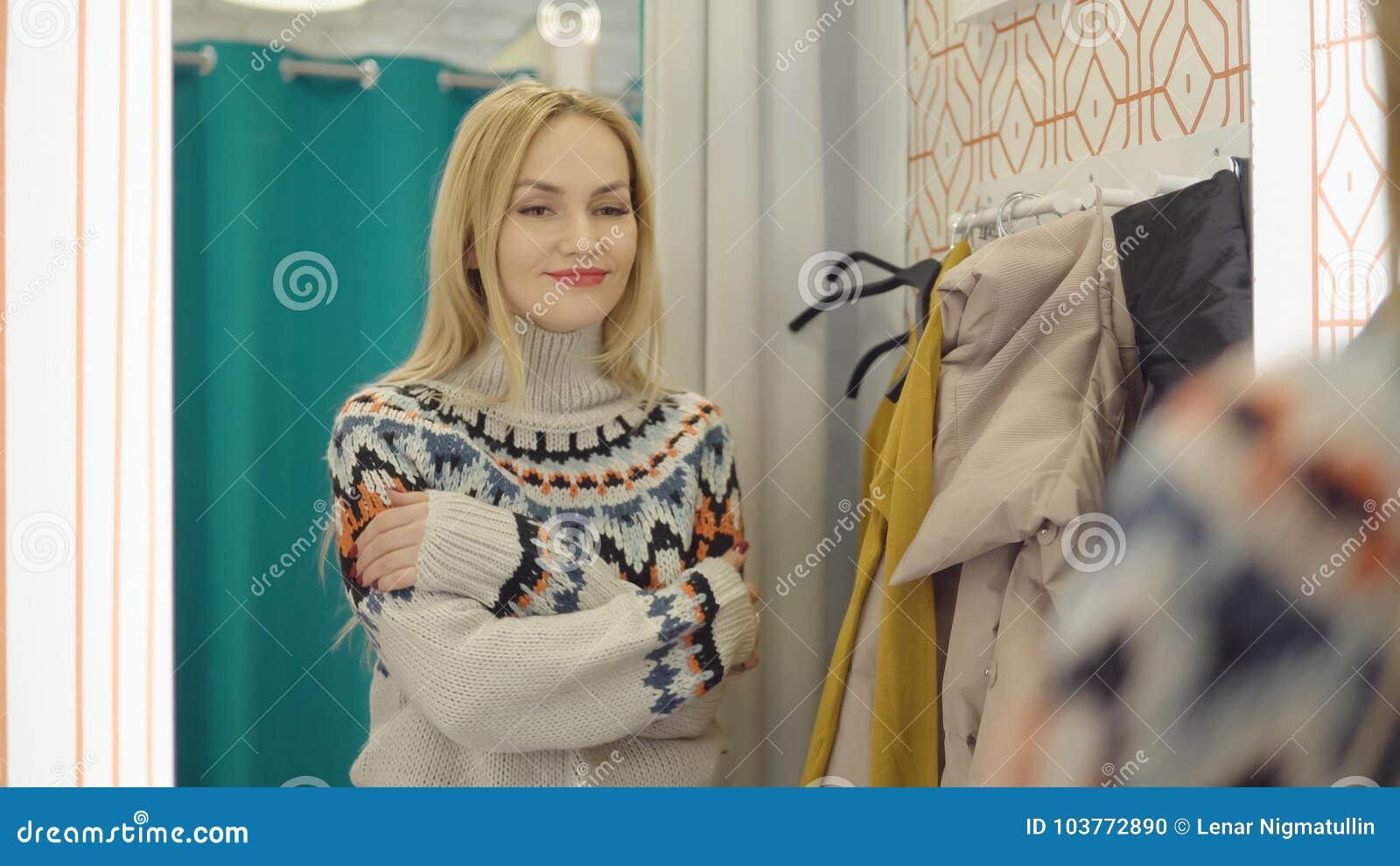 67ff578aaa1f Το νέο κορίτσι φαίνεται πουλόβερ κοντά στον καθρέφτη στο δωμάτιο  συναρμολογήσεων