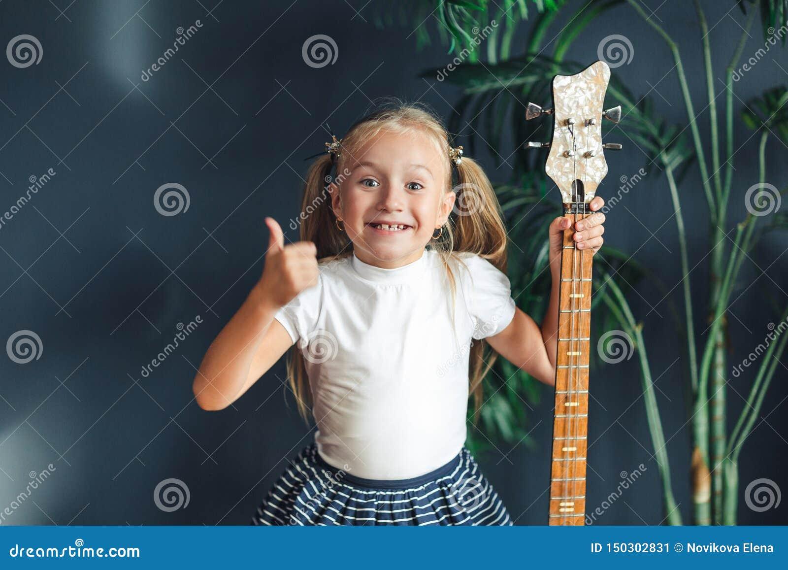 Το νέο ξανθό κορίτσι με τις ουρές στην άσπρα μπλούζα, τη φούστα και τα σανδάλια με την ηλεκτρική κιθάρα παρουσιάζει στο σπίτι αντ