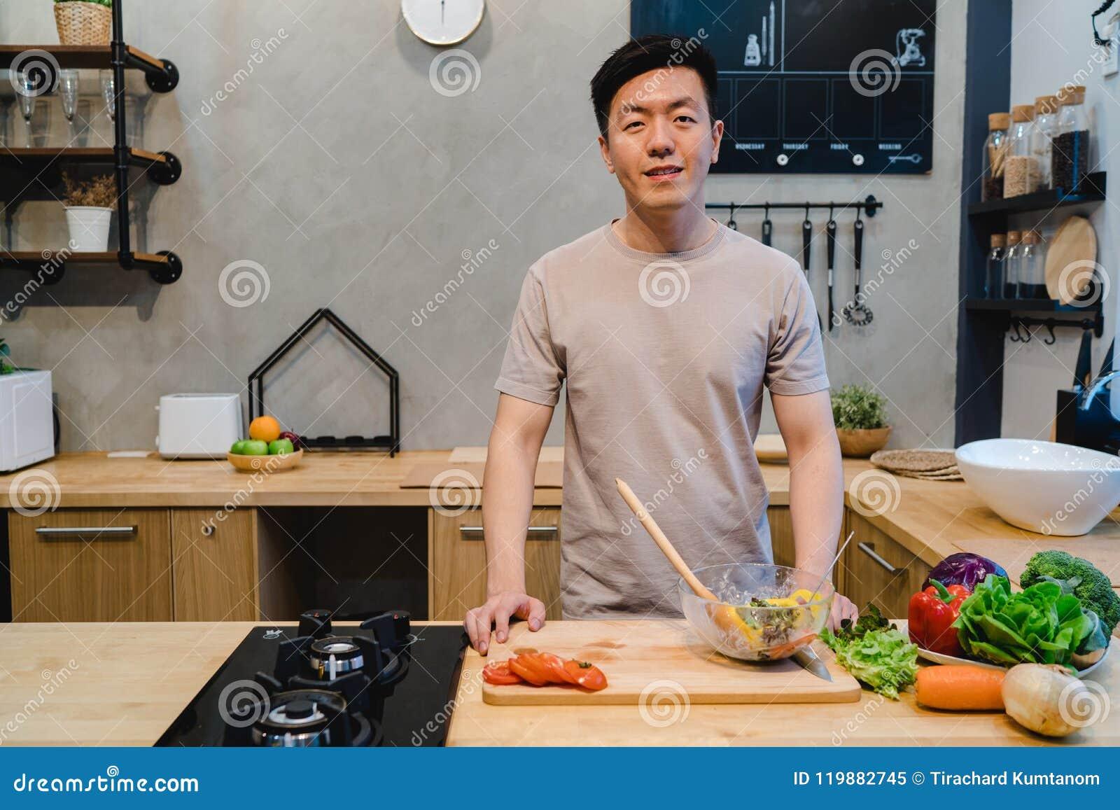 Το νέο όμορφο ασιατικό άτομο προετοιμάζει τα τρόφιμα και το μαγείρεμα σαλάτας στην κουζίνα