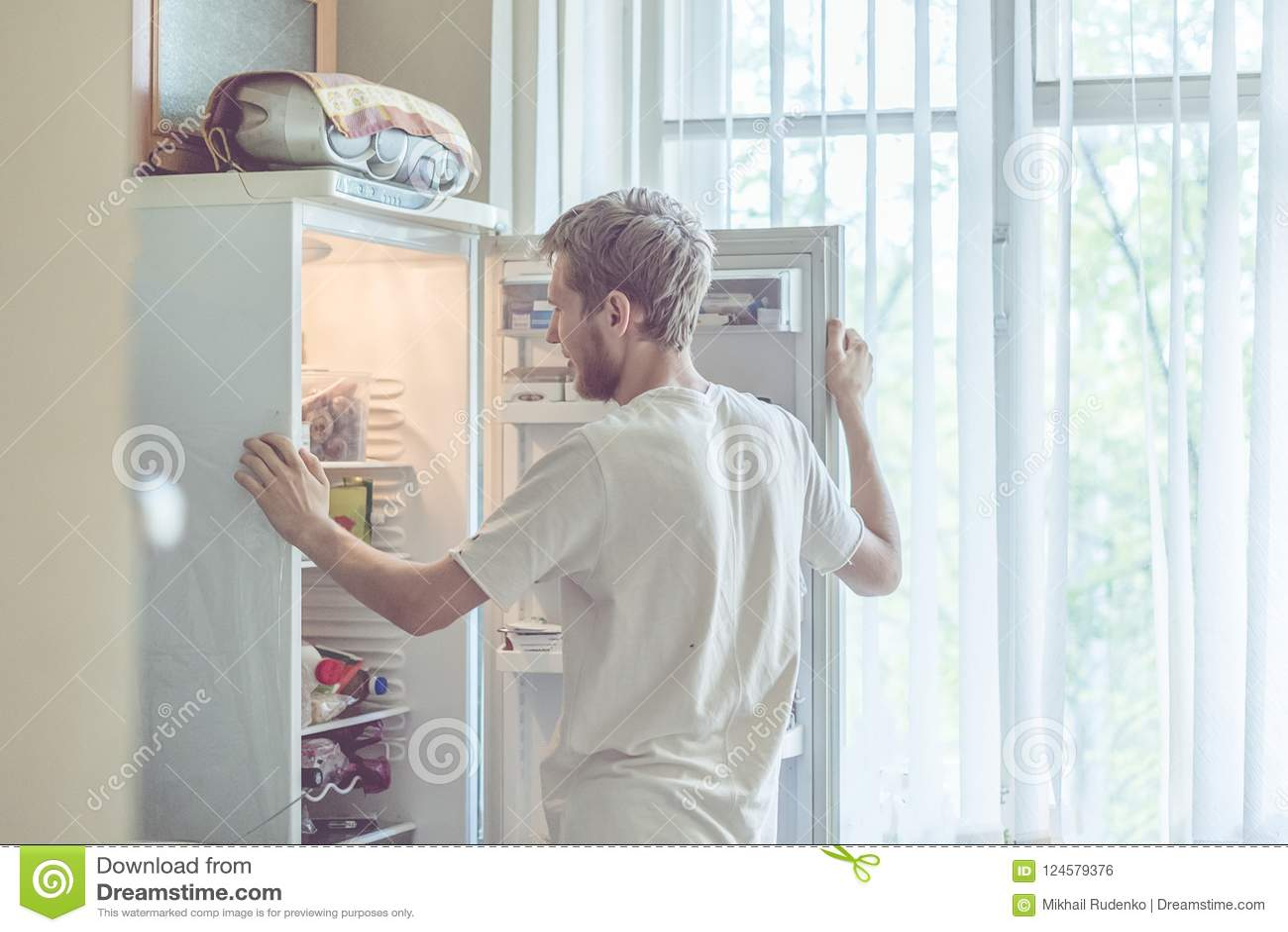 Το νέο όμορφο γενειοφόρο άτομο που στέκεται πλησίον η κουζίνα ψυγείων στο σπίτι