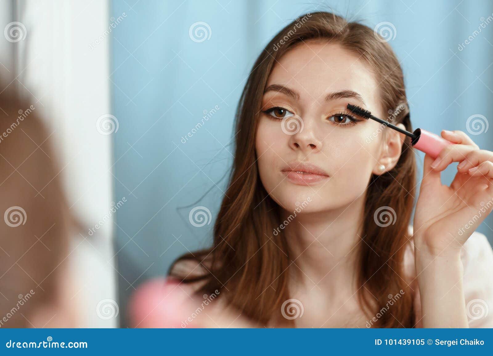 7d006fd9062e Το νέο όμορφο κορίτσι γίνεται ένα Makeup μπροστά από έναν καθρέφτη ...