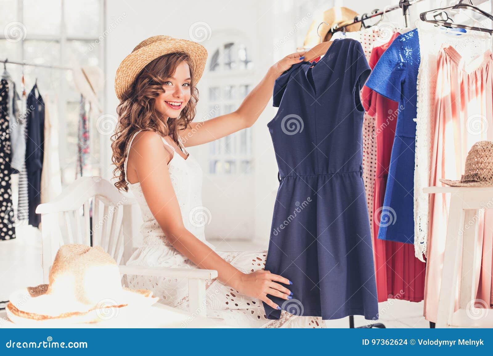 Το νέο όμορφο κορίτσι που επιλέγει και που προσπαθεί στα φορέματα στο κατάστημα