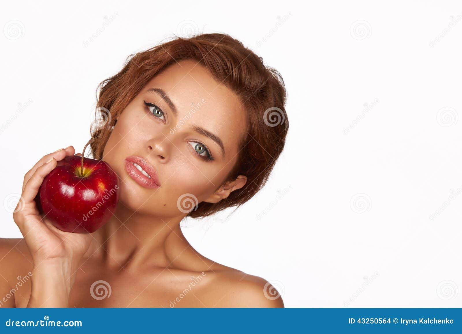 Το νέο όμορφο προκλητικό κορίτσι με τη σκοτεινή σγουρή τρίχα, τους γυμνούς ώμους και το λαιμό, που κρατούν το μεγάλο κόκκινο μήλο