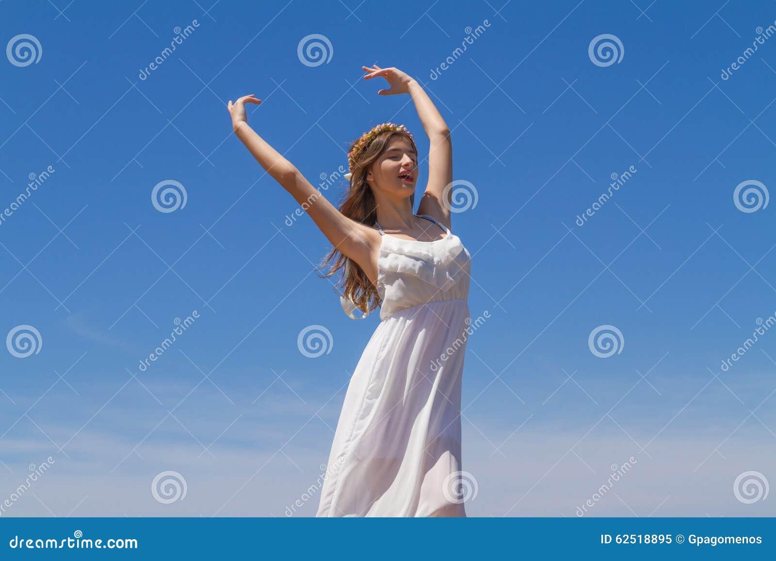 Το νέο brunette στο άσπρο ψιλό φόρεμα απολαμβάνει
