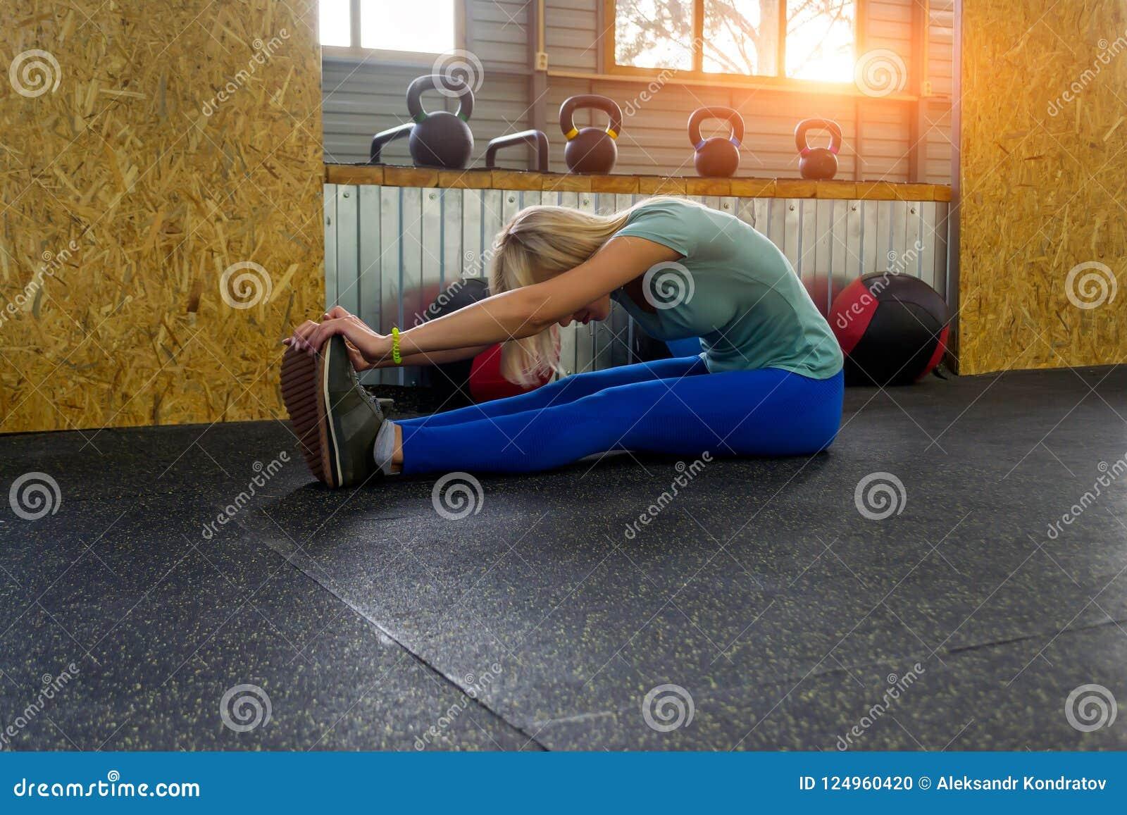 Το ξανθό κορίτσι κάνει το τέντωμα με το κάθισμα στο πάτωμα που κάμπτει το ο