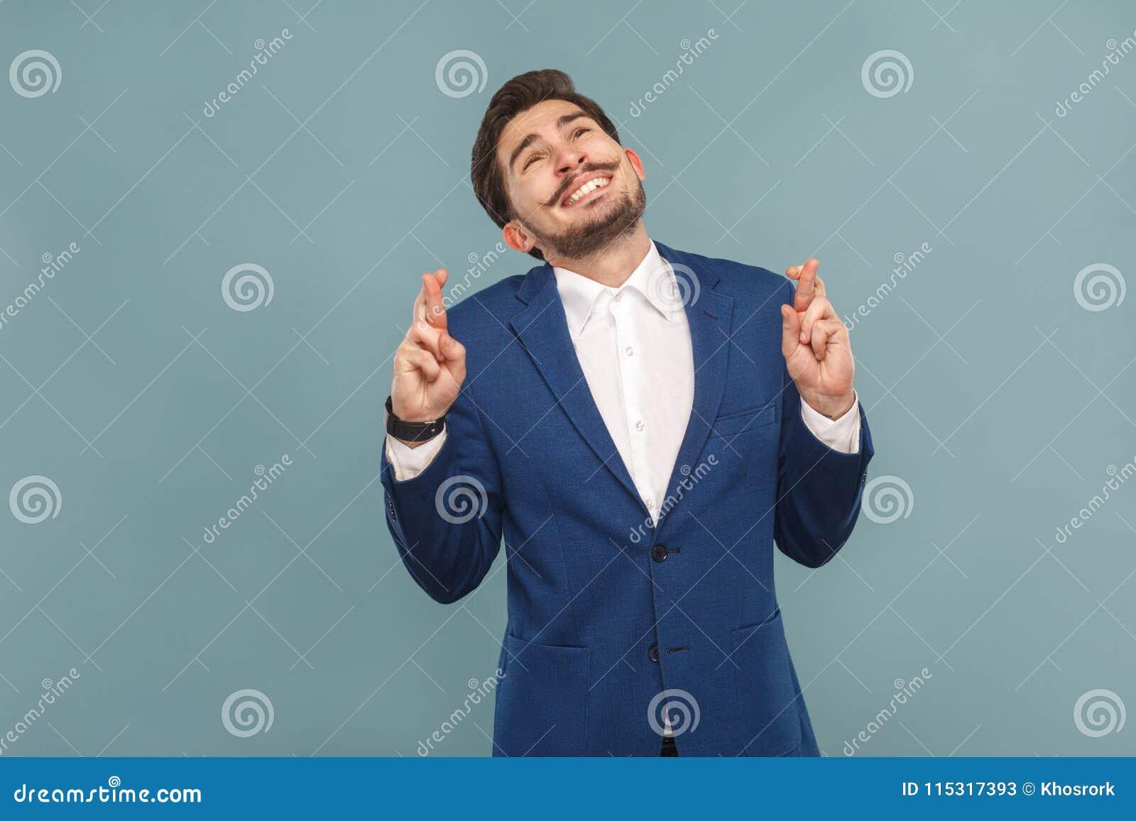 Το οδοντωτό χαμόγελο επιχειρησιακών ατόμων, διασχισμένη επιθυμία δάχτυλων, προσεύχεται και ελπίζει