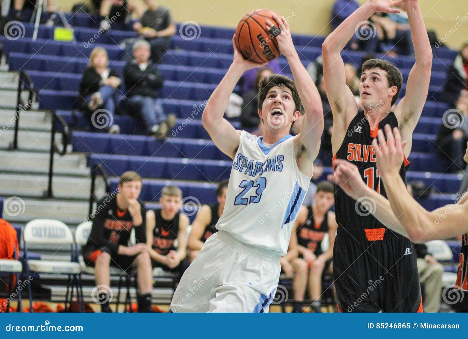 Το παίχτης μπάσκετ γυμνασίου Varsity ανεβαίνει για ένα καλάθι  φρουρημένος από τον αντίπαλο
