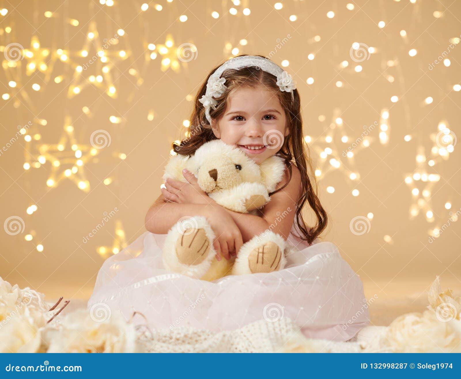 Το παιδί κοριτσιών με το παιχνίδι αρκούδων θέτει στα φω τα Χριστουγέννων, κίτρινο υπόβαθρο, ρόδινο φόρεμα