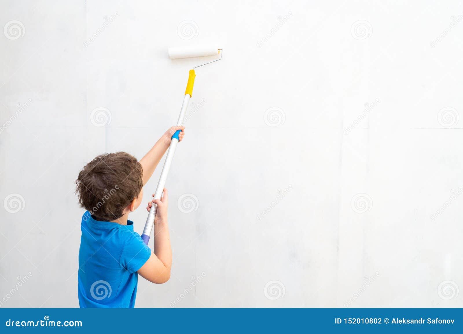 Το παιδί κυλά τον κύλινδρο στο χρώμα στον τοίχο η εργασία λήξης στις εγκαταστάσεις του καλλιτέχνη χρωματίζει τους τοίχους Επισκευ