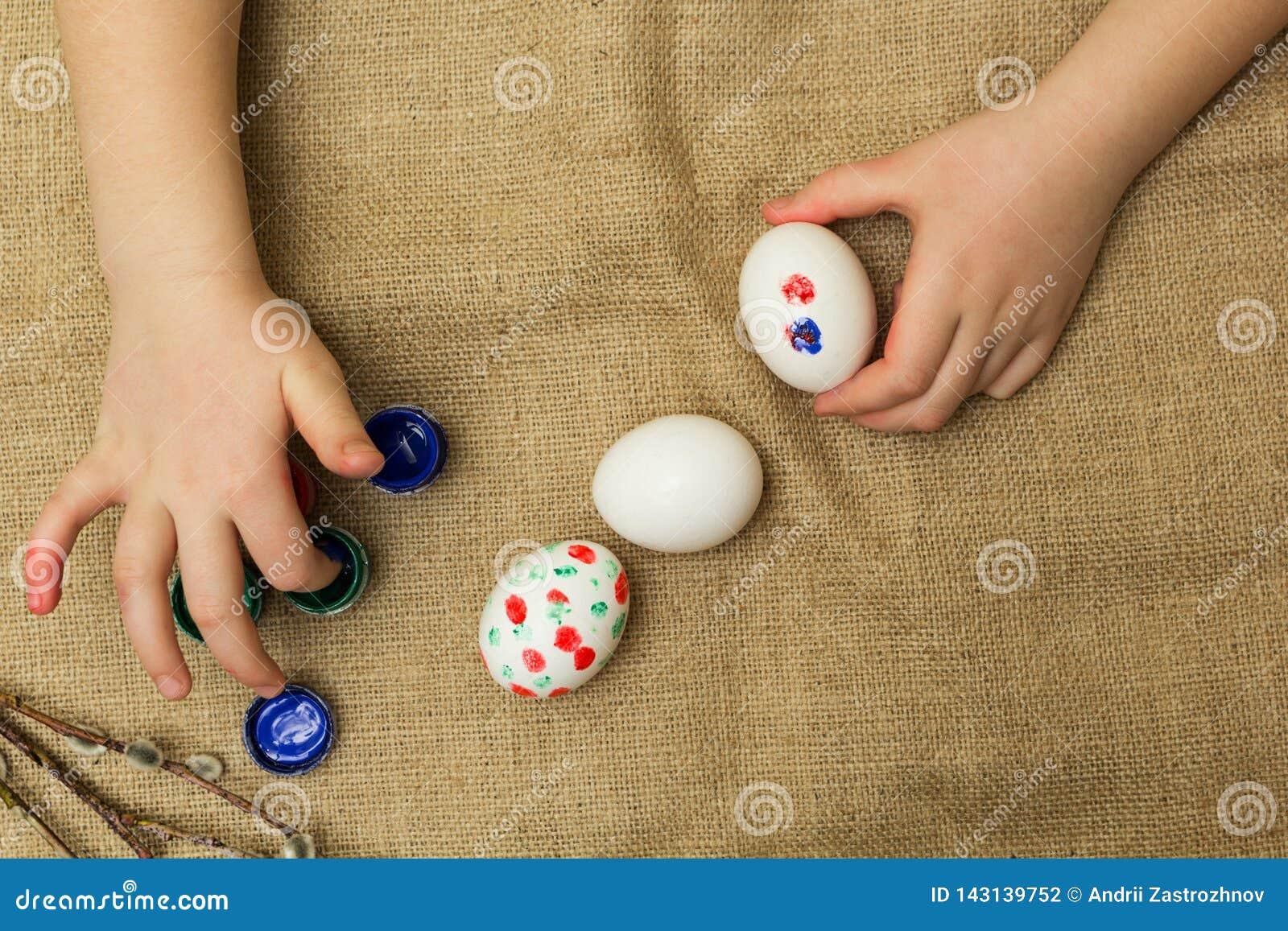 Το παιδί χρωματίζει τα αυγά για Πάσχα