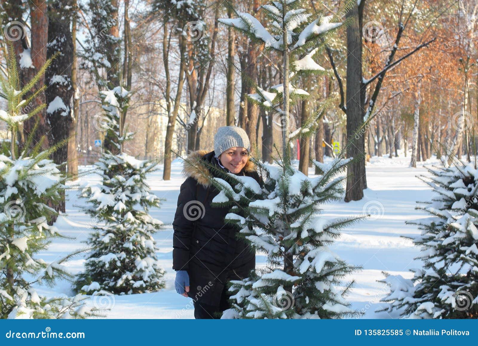 Το παιχνίδι νέων γυναικών και νεαρών άνδρων συσσωρεύεται snowdrift μεταξύ των δέντρων που καλύπτονται στο χιόνι
