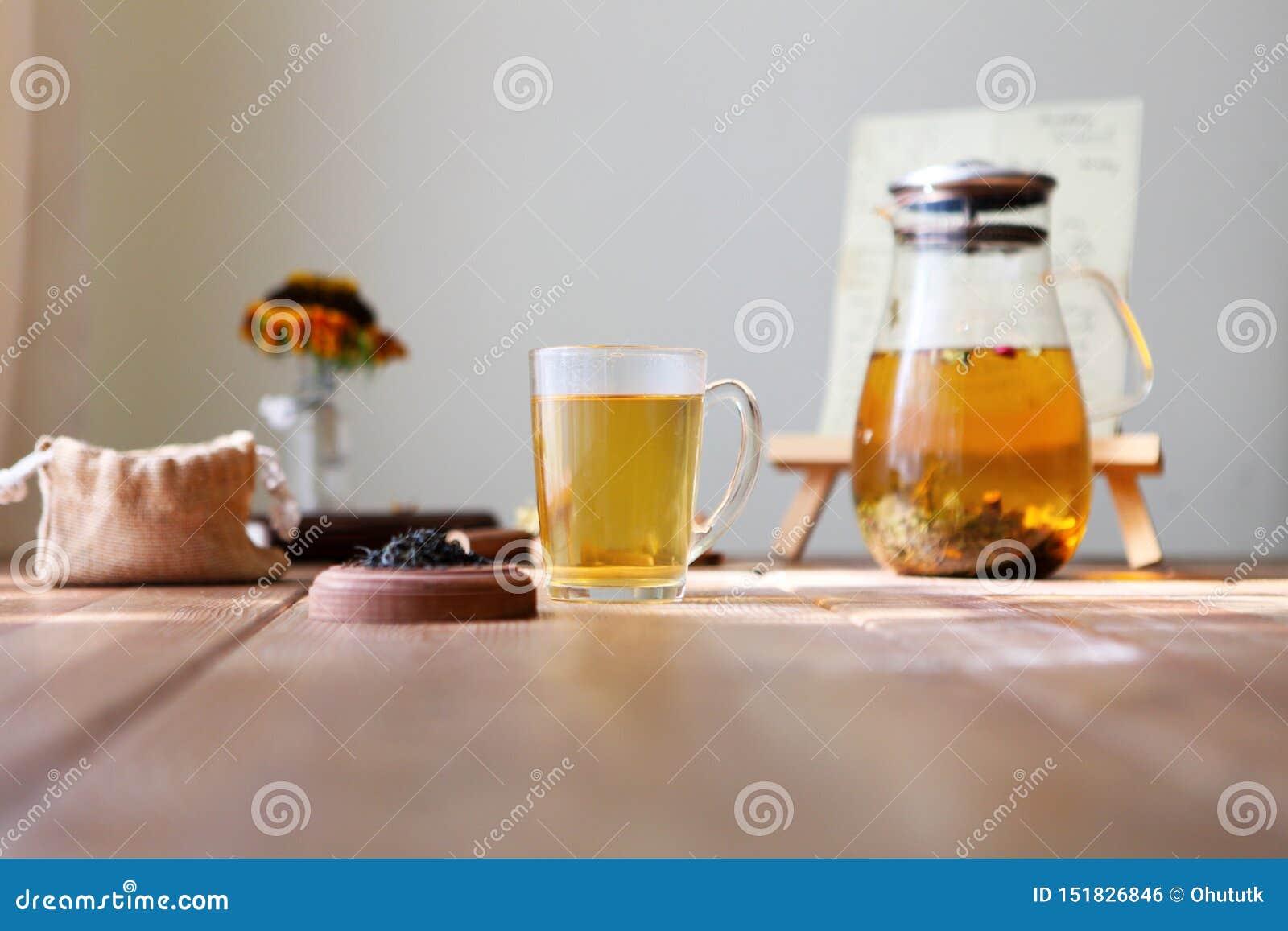 Το παραδοσιακό heral τσάι με teapot γυαλιού, φλυτζάνι, ξηρό αυξήθηκε οφθαλμοί Λουλούδια στον ξύλινο πίνακα στο σπίτι, υπόβαθρο φω