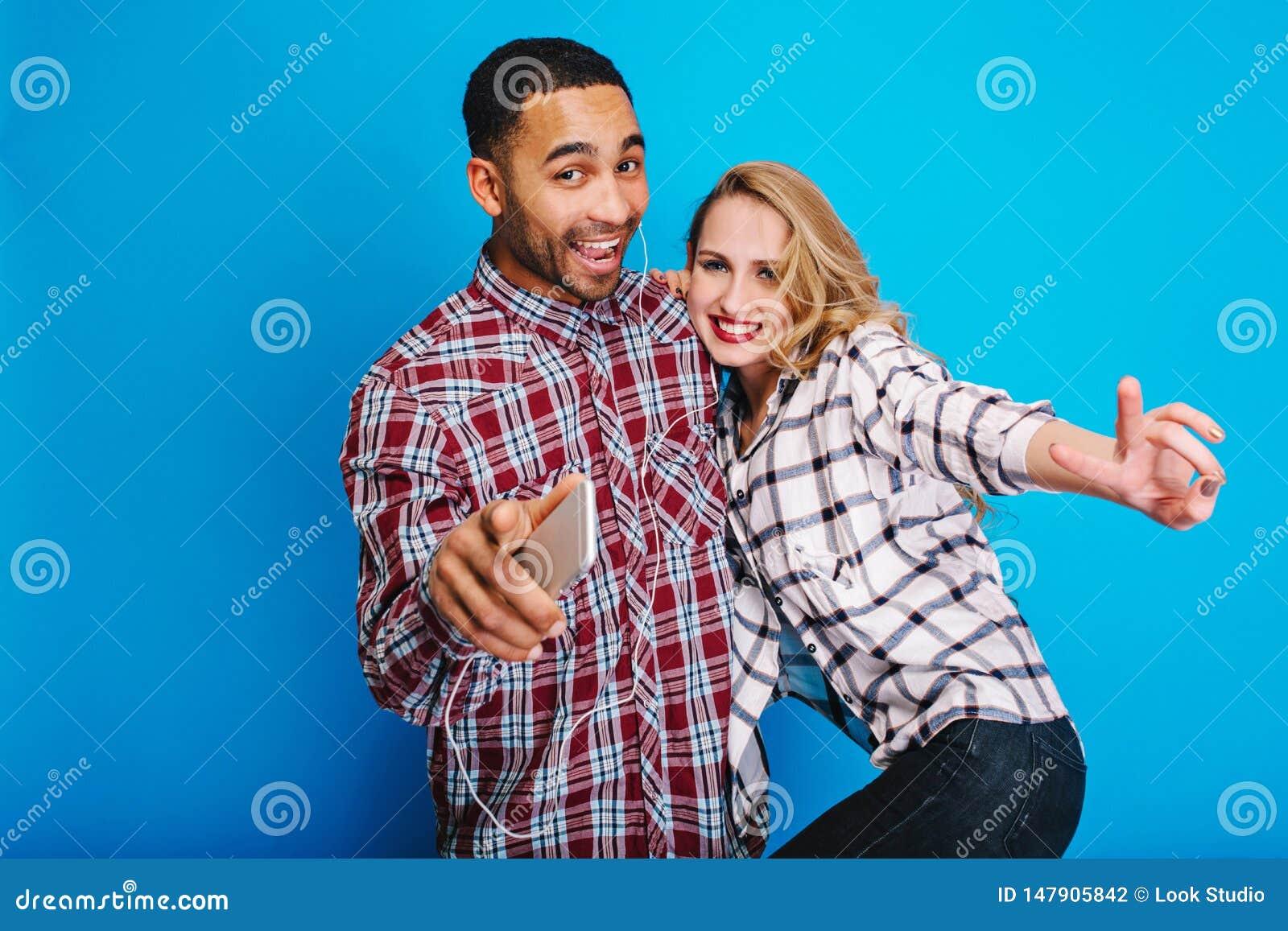 Το πορτρέτο διέγειρε το ζεύγος που έχει τη διασκέδαση μαζί, ακούοντας τη μουσική μέσω των ακουστικών στο μπλε υπόβαθρο Μοντέρνη π