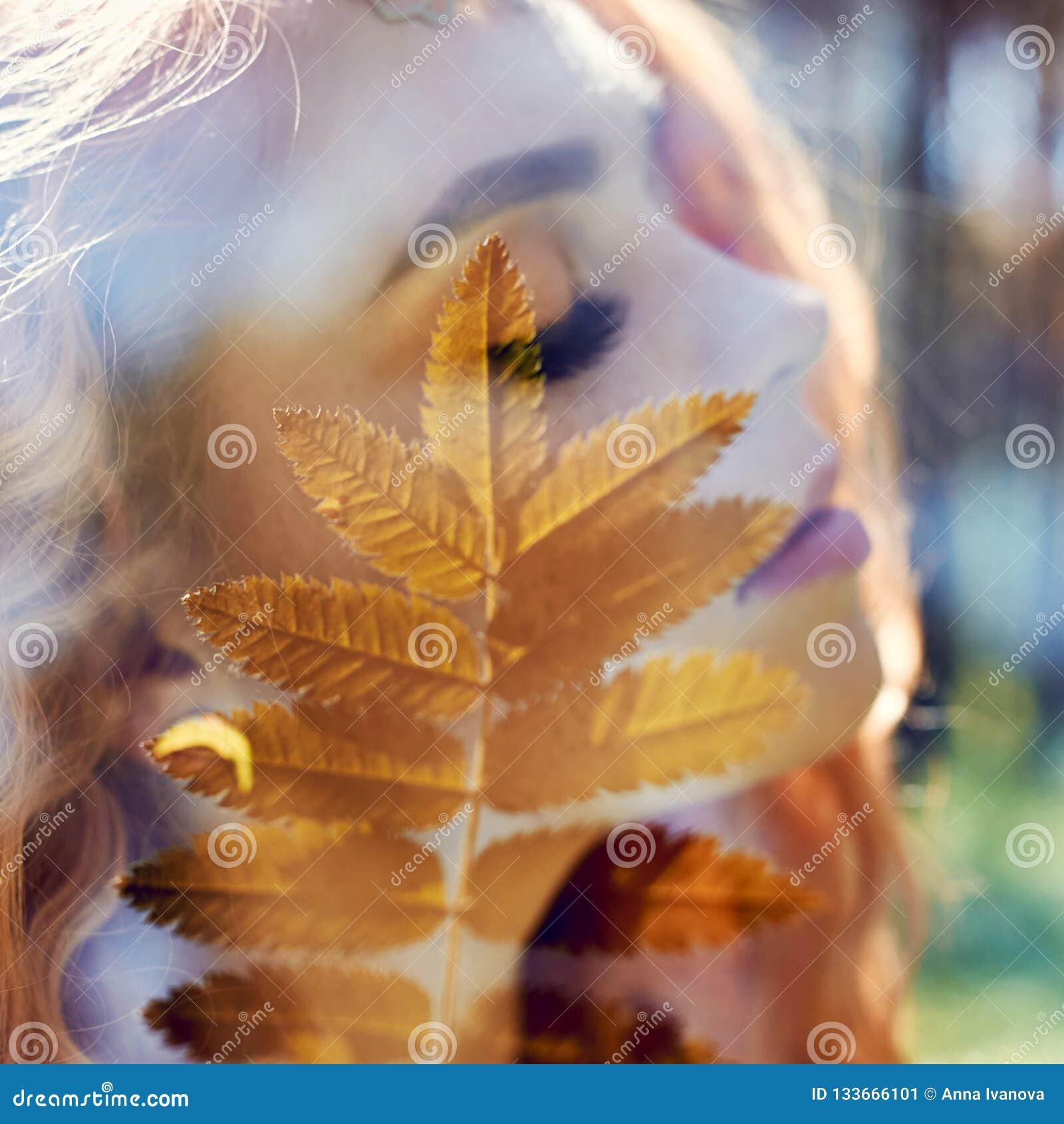 Το πορτρέτο μιας γυναίκας με μια διπλή έκθεση, το κορίτσι και τη θολωμένη φύση της φωτογραφίας δεν είναι στην εστίαση Τα φύλλα στ