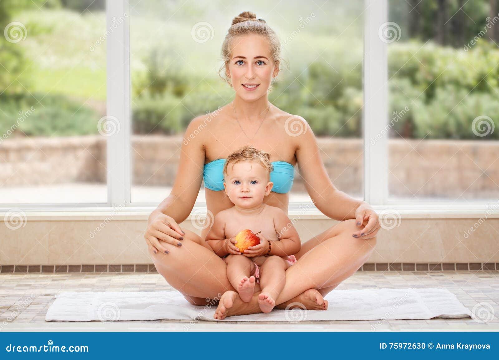 Το πορτρέτο ομάδας της λευκιάς καυκάσιας κόρης μητέρων και μωρών που κάνει τη γιόγκα ασκήσεων φυσικής ικανότητας που κάθεται μαζί