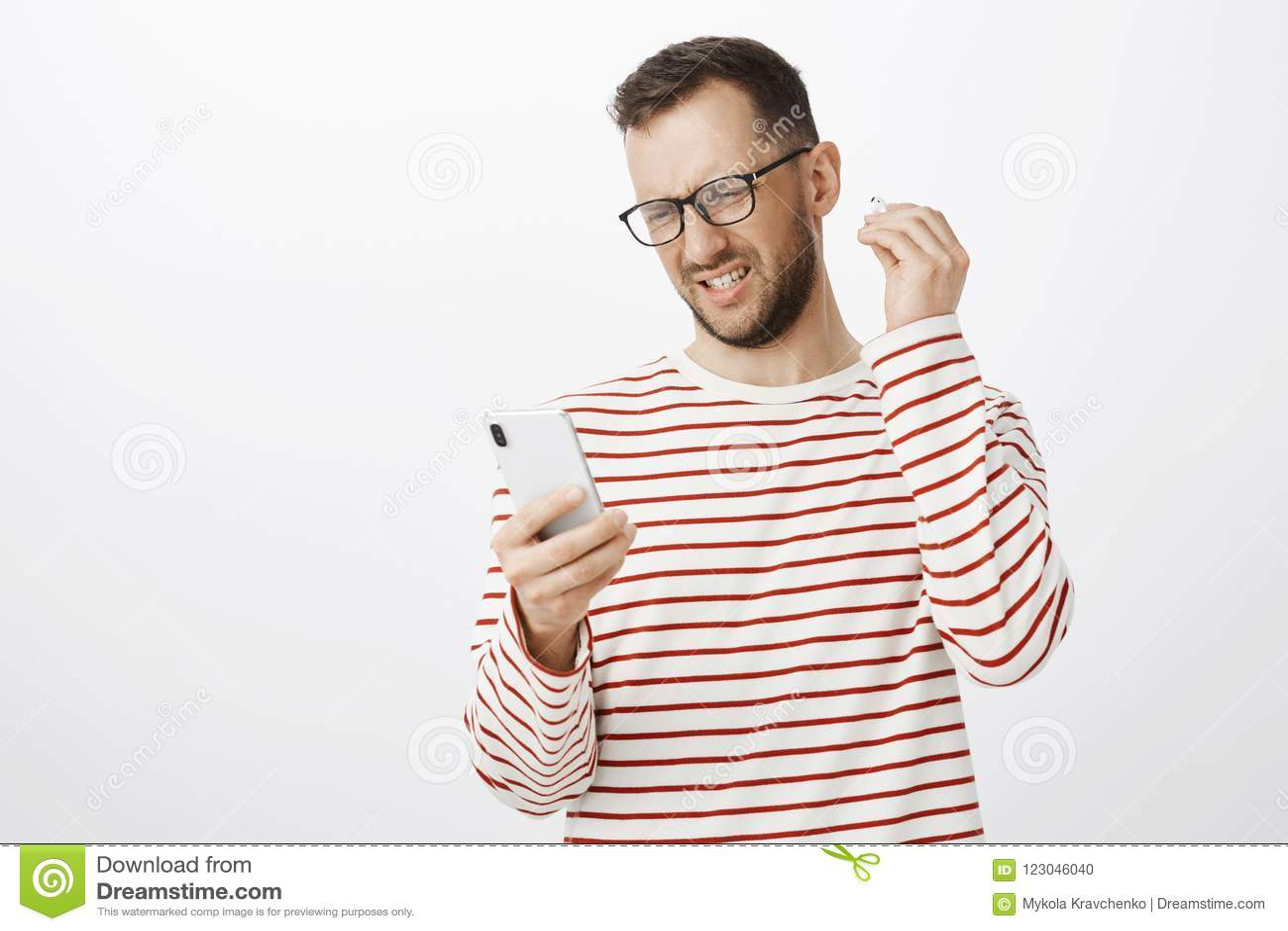 Το πορτρέτο ο ματαιωμένος ευρωπαϊκός τύπος στο ριγωτά πουλόβερ και τα γυαλιά, που βγάζουν το ασύρματο ακουστικό και