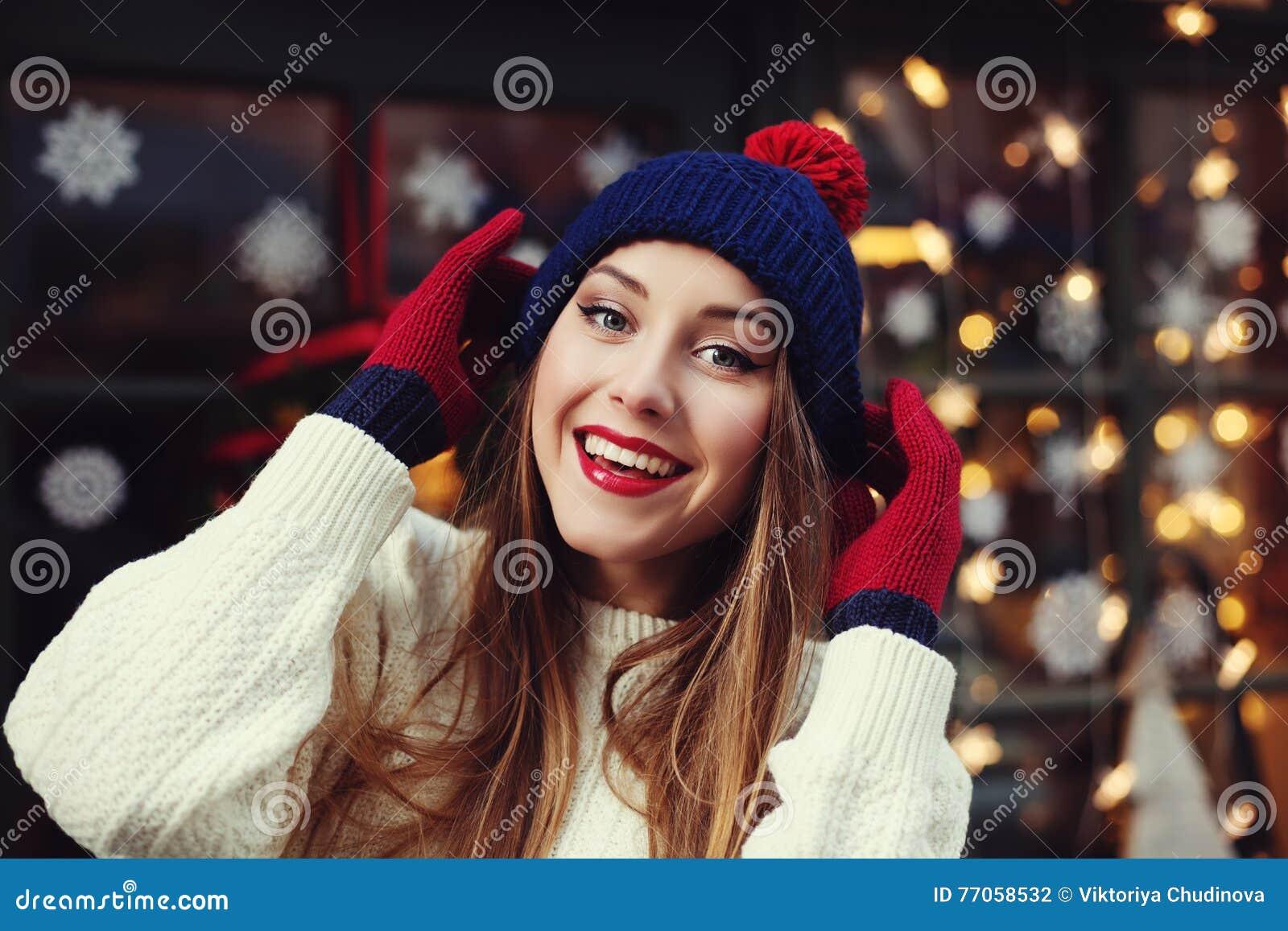 Το πορτρέτο οδών της χαμογελώντας όμορφης νέας γυναίκας που φορά το μοντέρνο κλασικό χειμώνα έπλεξε τα ενδύματα Πρότυπη εξέταση τ