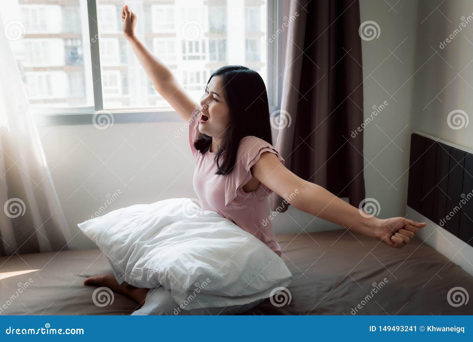 Το πορτρέτο της ασιατικής γυναίκας τεντώνει τα χέρια της στην κρεβατοκάμαρα μετά από ξυπνήστε, την υγειονομική περίθαλψη και την