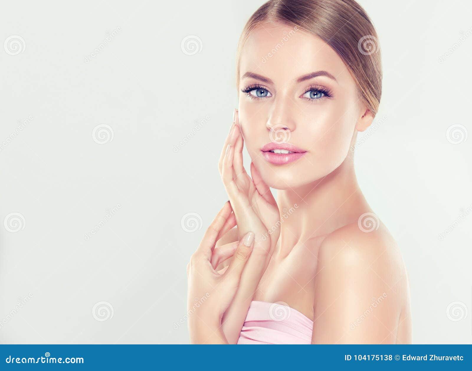 Το πορτρέτο της νέας γυναίκας με το καθαρό φρέσκο δέρμα και μαλακός, λεπτό αποτελεί Η γυναίκα αγγίζει tenderly για να είναι κύρια