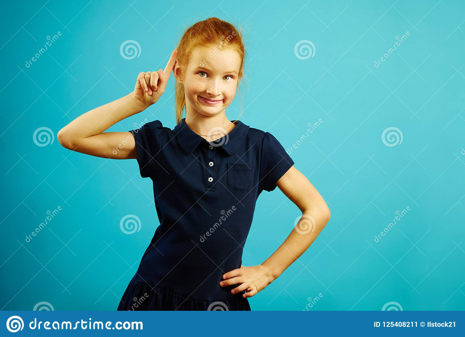 Το πορτρέτο του ευφυούς κοκκινομάλλους κοριτσιού με τον αυξημένο δείκτη προς τα πάνω, έχει ένα ευτυχές εκφραστικό πρόσωπο, εκφράζ