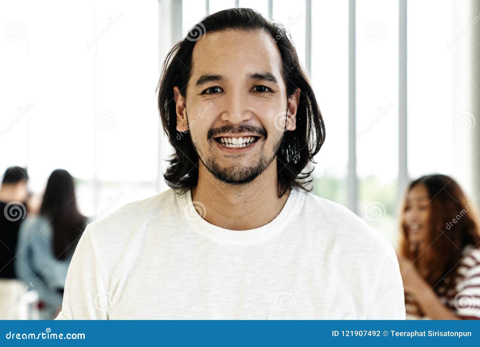 Το πορτρέτο του νέου ευτυχούς κοντού μοντέρνου γενειοφόρου ασιατικού ατόμου ή ο δημιουργικός σχεδιαστής χαμογελά και εξετάζοντας