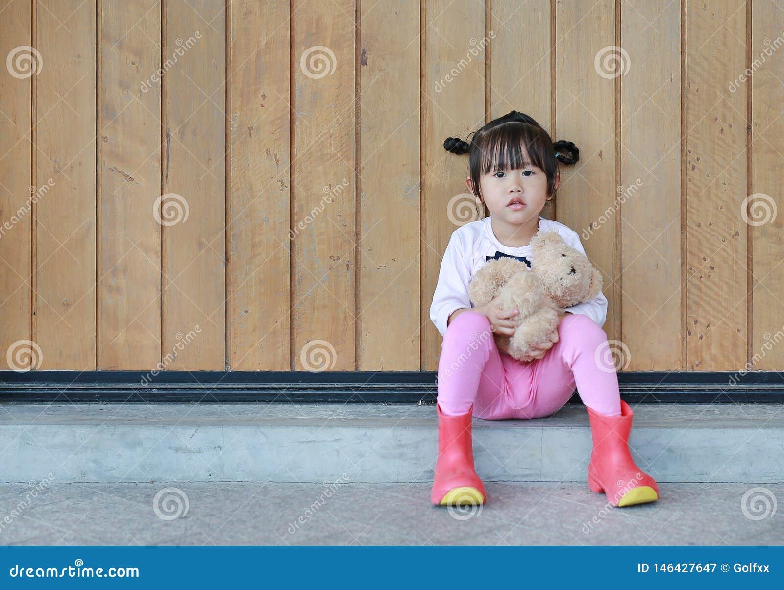 Το πορτρέτο του χαριτωμένου μικρού κοριτσιού κάθεται και αγκαλιάζοντας Teddy αντέξτε ενάντια στον ξύλινο τοίχο σανίδων