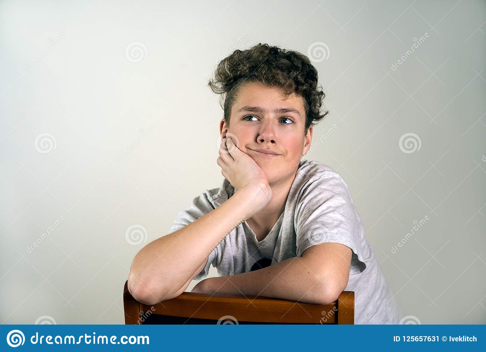 Το πορτρέτο του χαριτωμένου χαμογελώντας αγοριού κάθεται στην καφετιά καρέκλα στο γκρίζο β