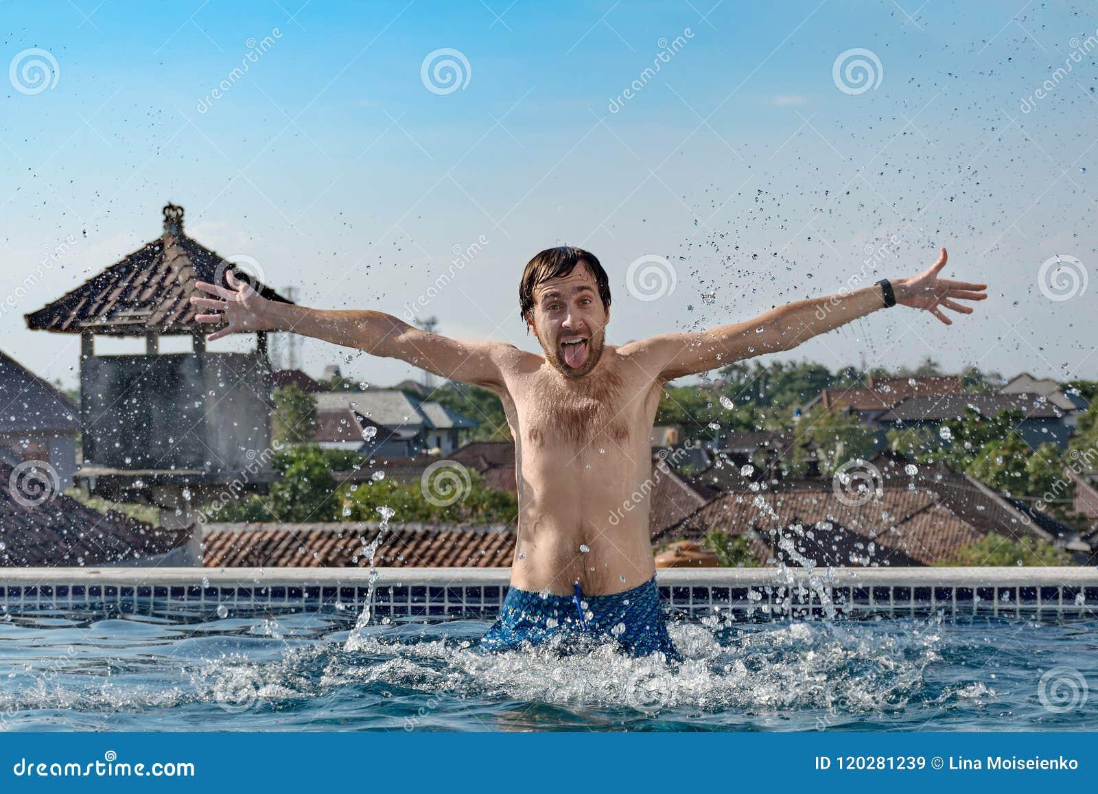 Το πορτρέτο του χαρούμενου λεπτού ατόμου με τη θωρακική τρίχα, προκύπτει από τη λίμνη, παφλασμοί νερού, παρουσιάζει τη γλώσσα και