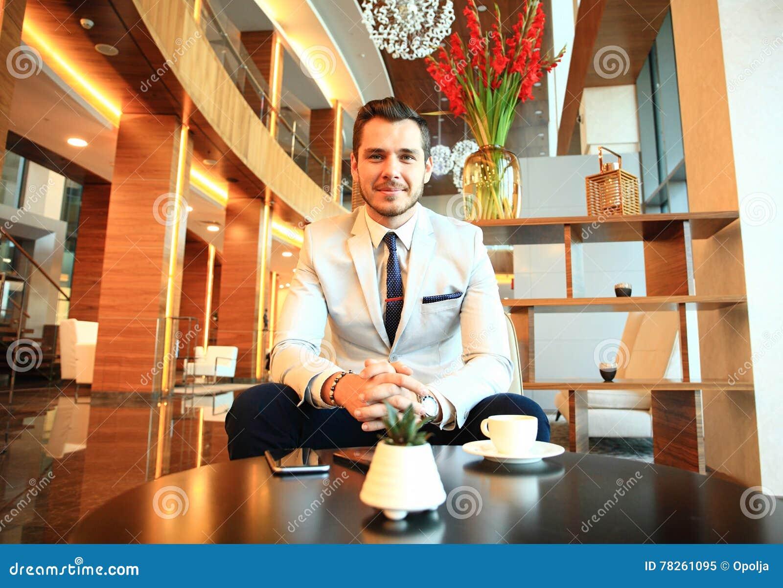 Το πορτρέτο του όμορφου επιτυχούς ατόμου πίνει τη συνεδρίαση καφέ στη καφετερία, επιχειρησιακό άτομο που έχει το πρόγευμα στο λόμ
