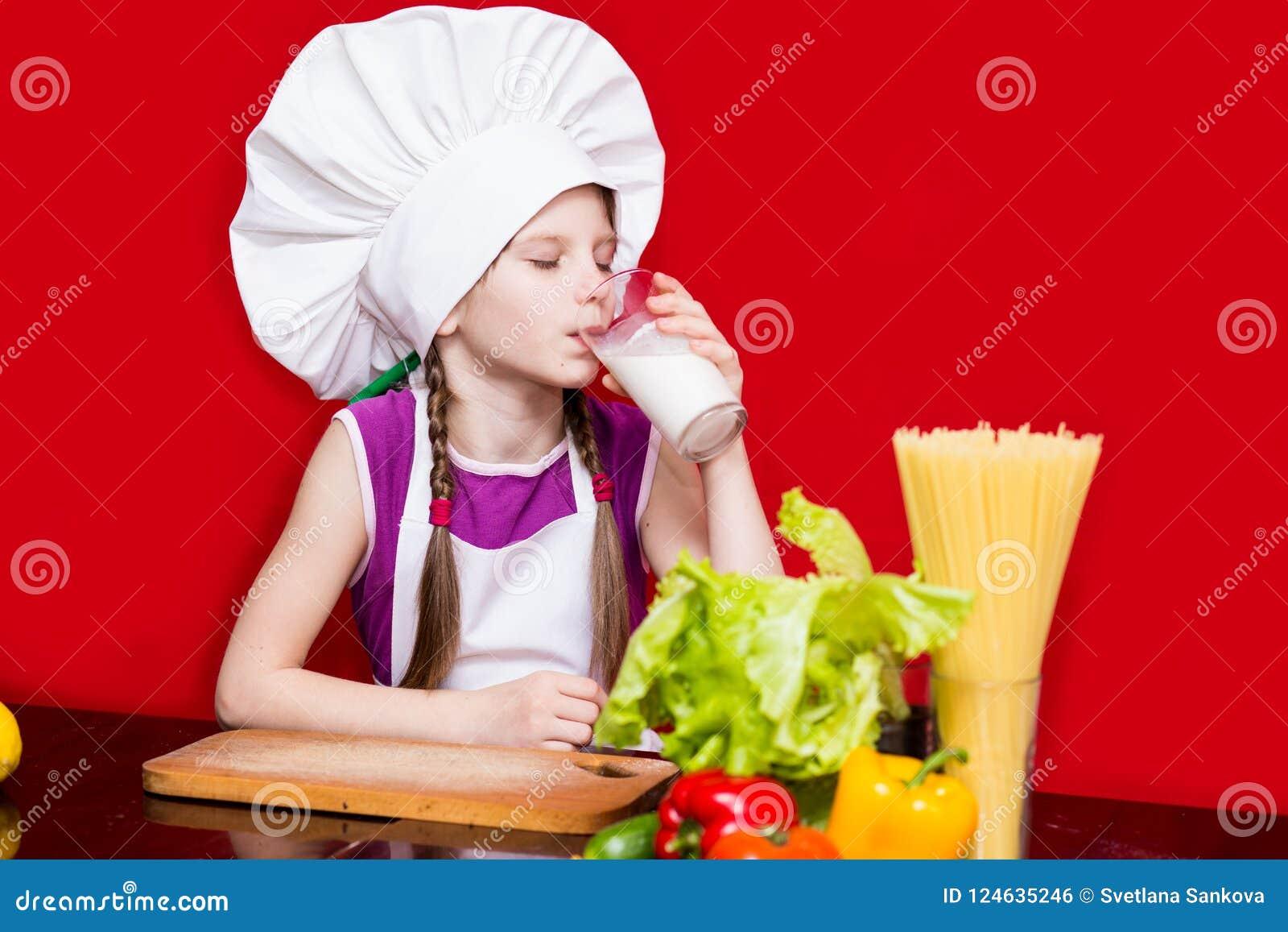 Το πορτρέτο του όμορφου μικρού κοριτσιού με μορφή μάγειρα που απομονώνεται στο κόκκινο πίνει το γάλα