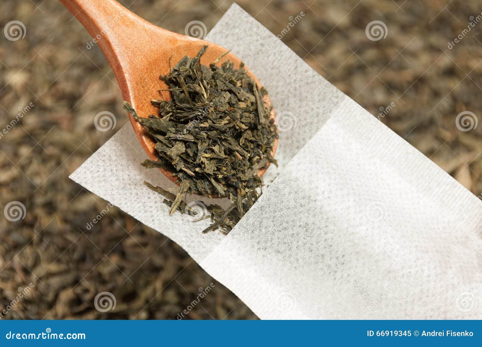 Το πράσινο τσάι γεμίζουν με το ξύλινο κουτάλι σε ένα ειδικό φίλτρο τσαγιού