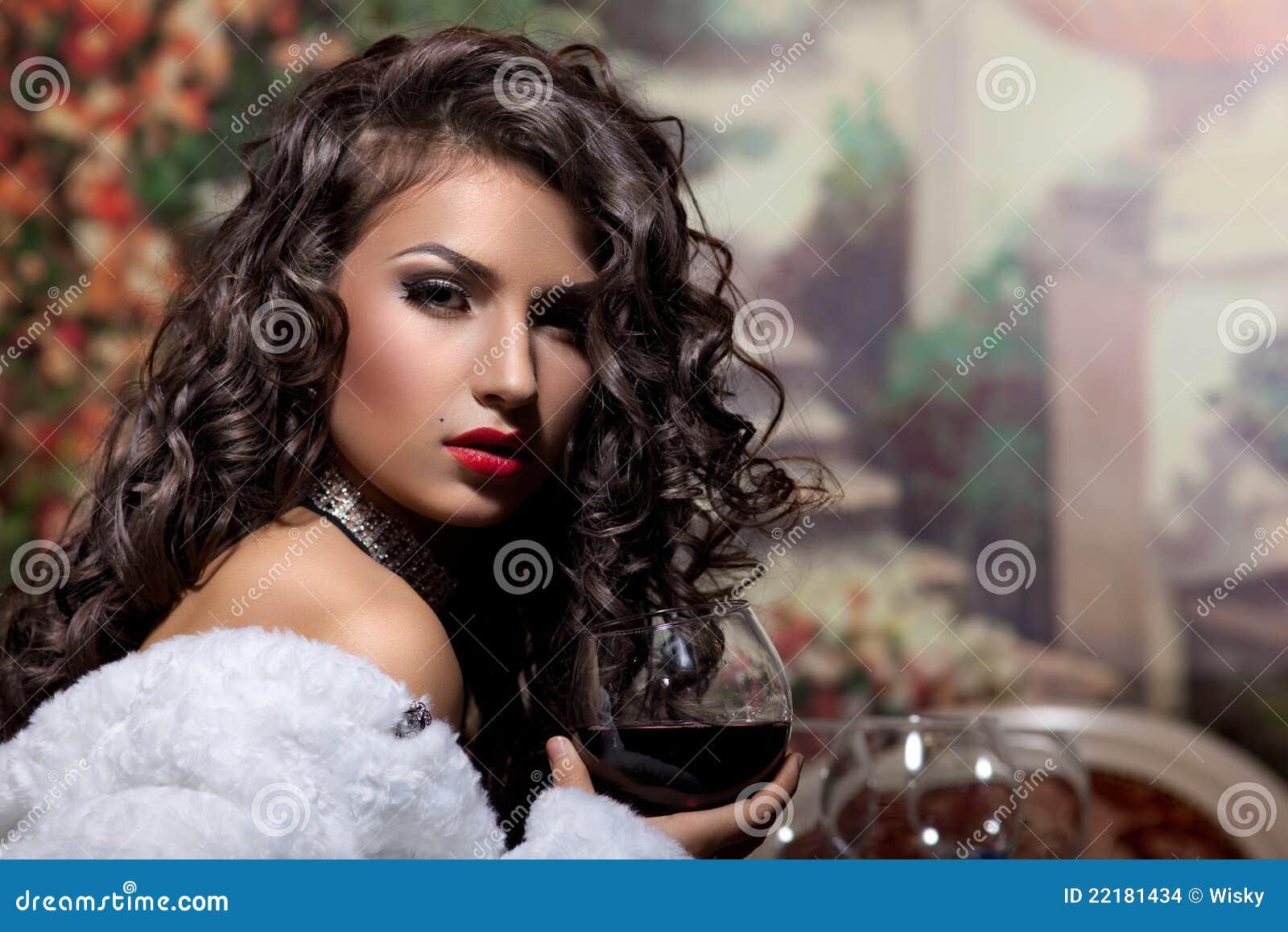 Το προκλητικό κορίτσι κάθεται με το κρασί στο παλτό γουνών στο βράδυ
