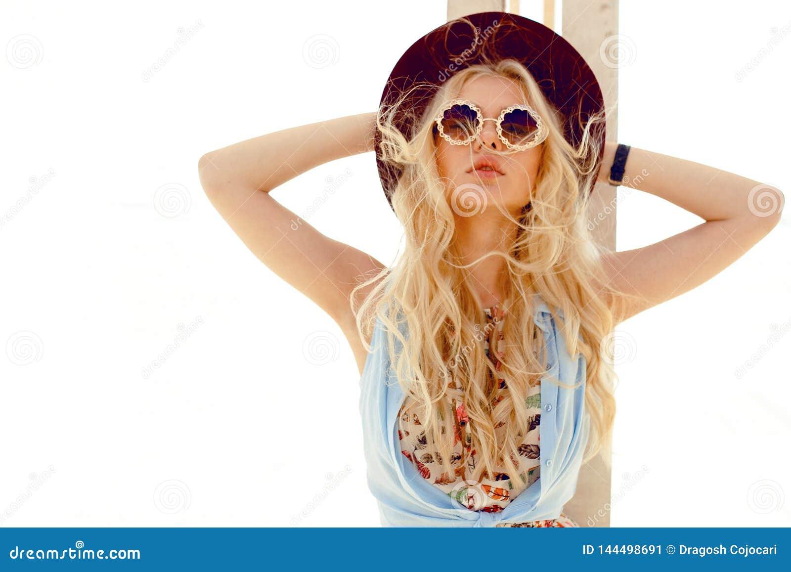 Το προκλητικό ξανθό κορίτσι με τα στρογγυλά γυαλιά ηλίου, το πουκάμισο τζιν, το χαριτωμένο φόρεμα, την τρίχα κυμάτων και burgundy