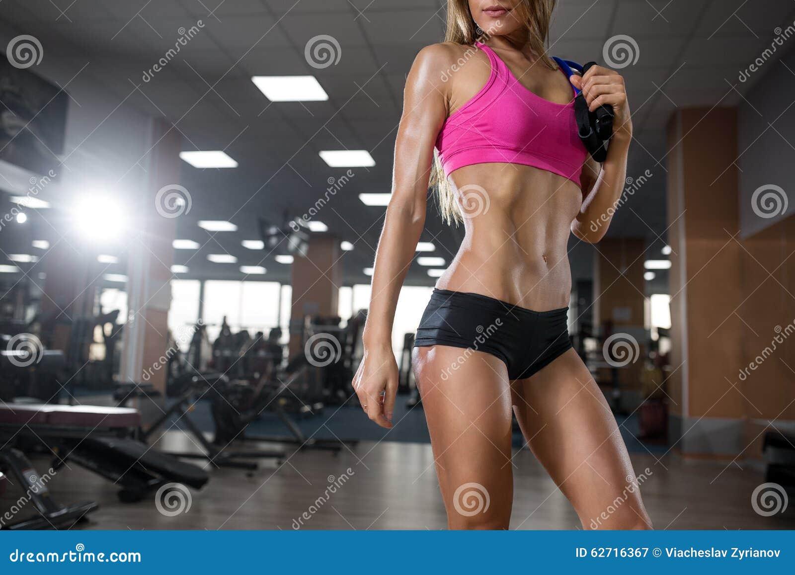 Το προκλητικό όμορφο νέο κορίτσι ικανότητας εκτελεί την άσκηση με τον αποσυμπιεστή στη γυμναστική