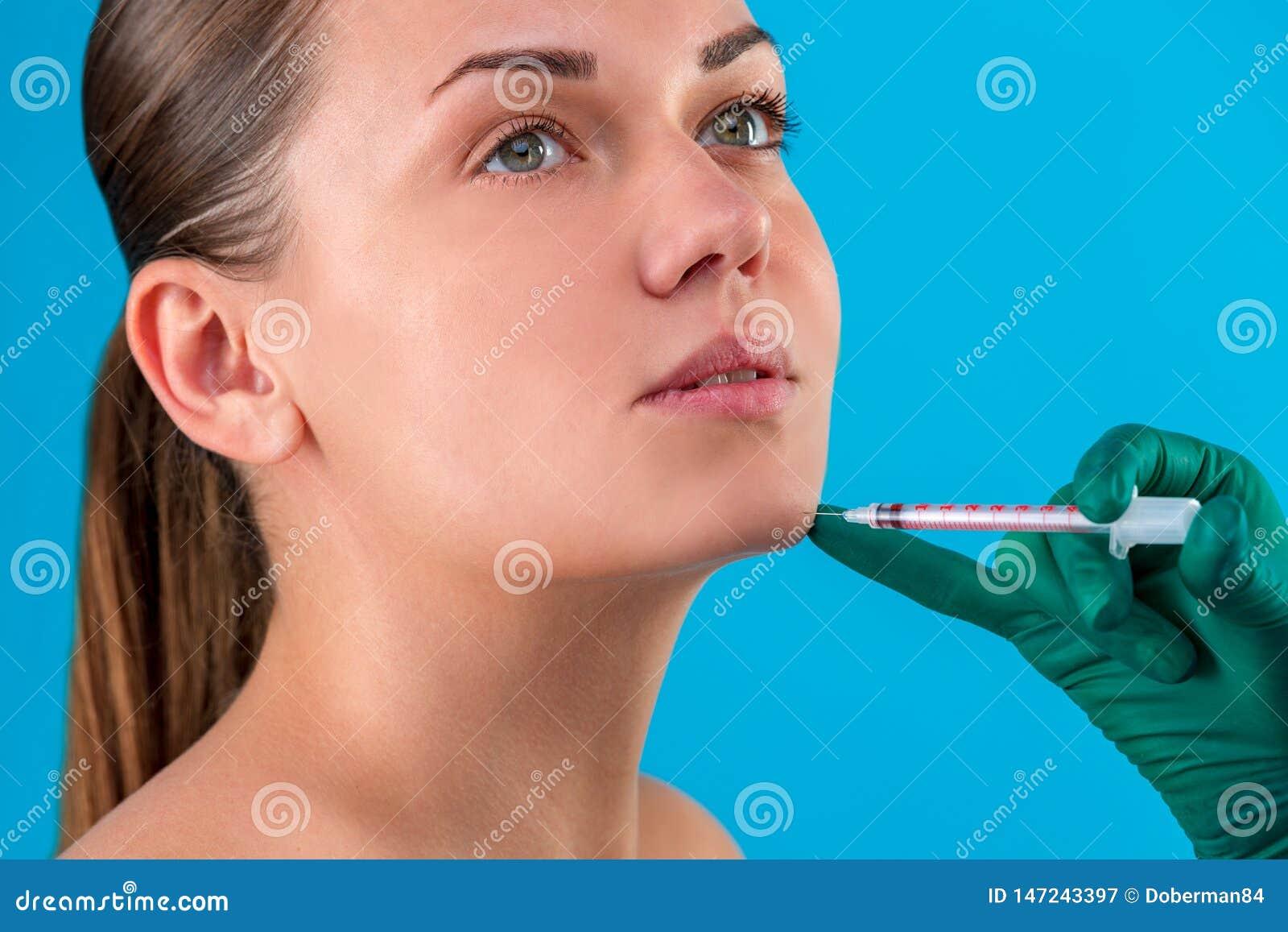 Το πρόσωπο ενός κοριτσιού με το ομαλό δέρμα χωρίς ρυτίδες κάνει τους πυροβολισμούς ομορφιάς Σύριγγα δίπλα στο πρόσωπο, σαλόνι φρο