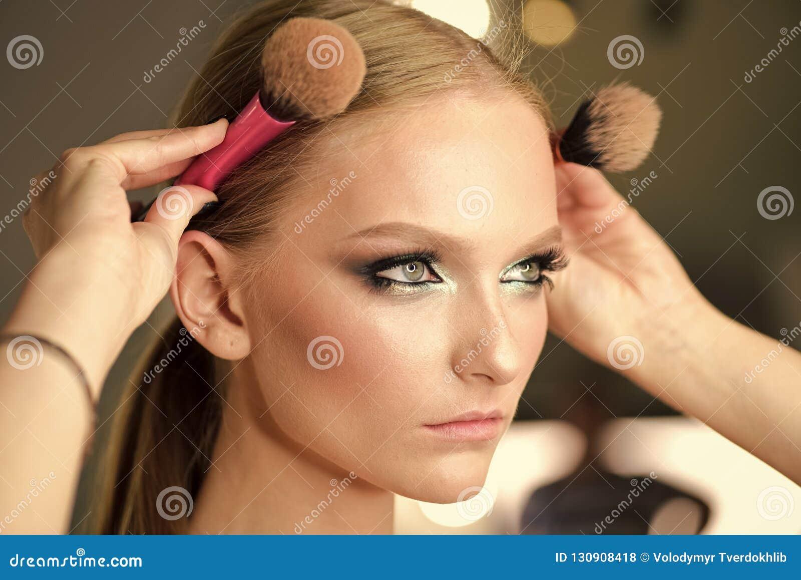 Το πρότυπο ομορφιάς με τη γοητεία κοιτάζει, hairstyle Γυναίκα με τις βούρτσες λαβής προσώπου makeup στο κεφάλι Γυναίκα με τα ξανθ
