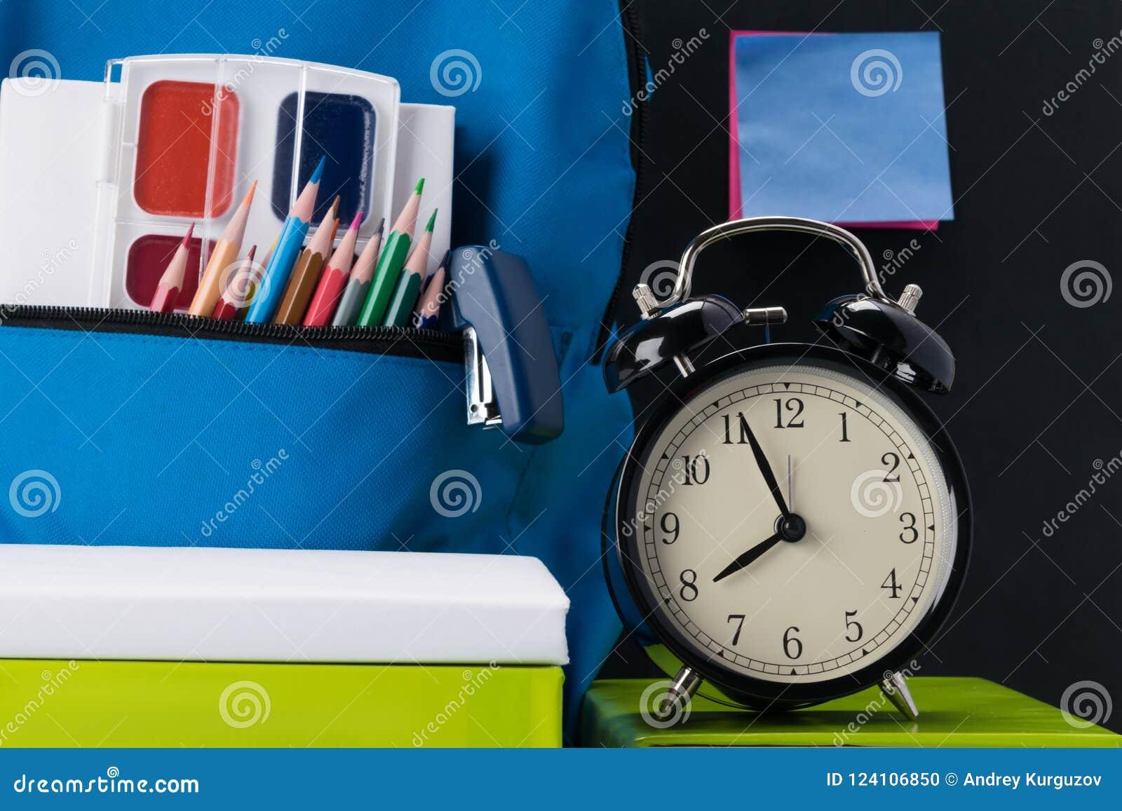 Το ρολόι δείχνει ότι ο χρόνος του να πάει στο σχολείο και τα σχολικά πράγματα στον πίνακα