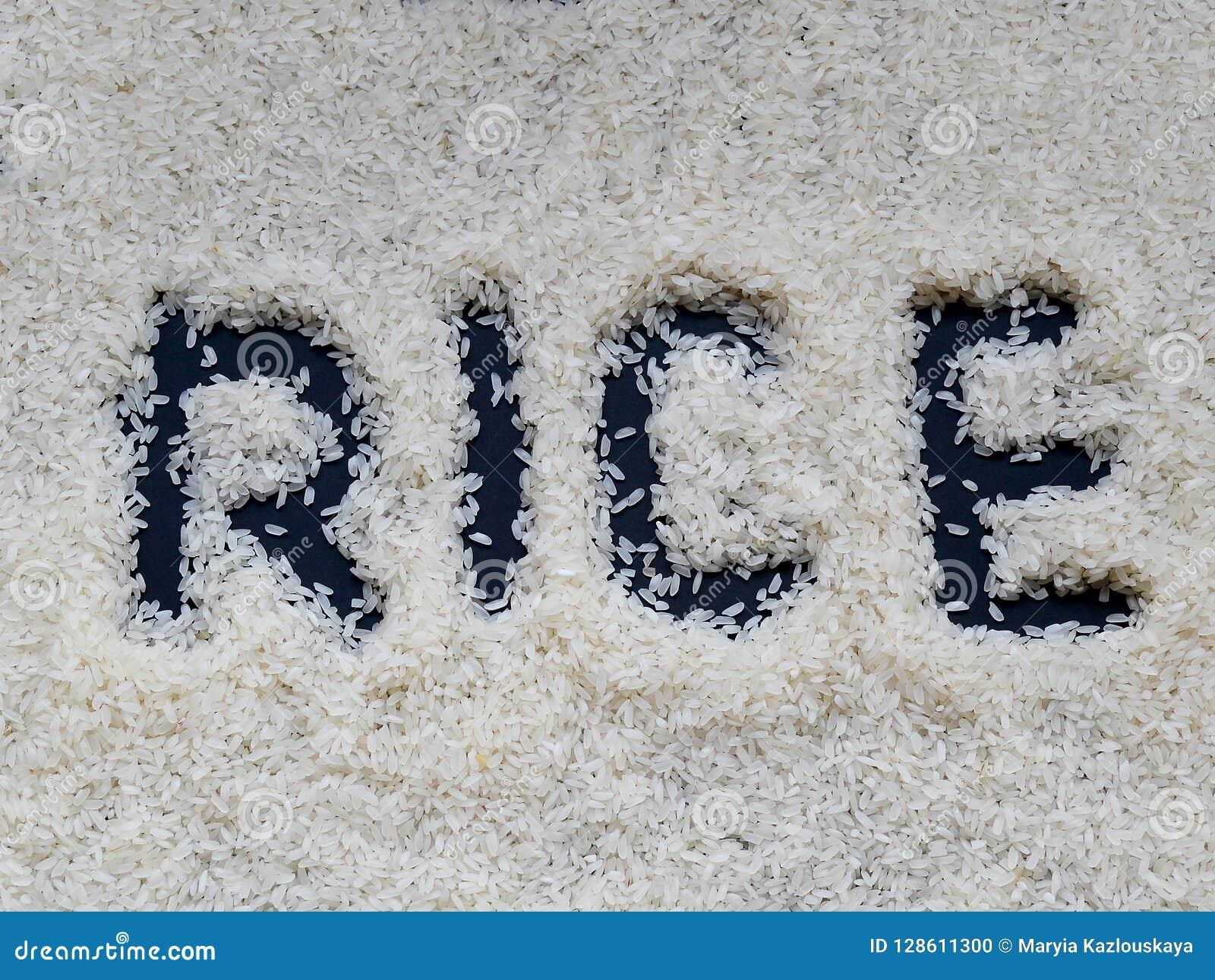 Το ρύζι ` λέξης ` που γράφεται με ένα δάχτυλο σε ένα στρώμα του άσπρου ακατέργαστου ρυζιού που βρίσκεται σε ένα σκοτεινό υπόβαθρο