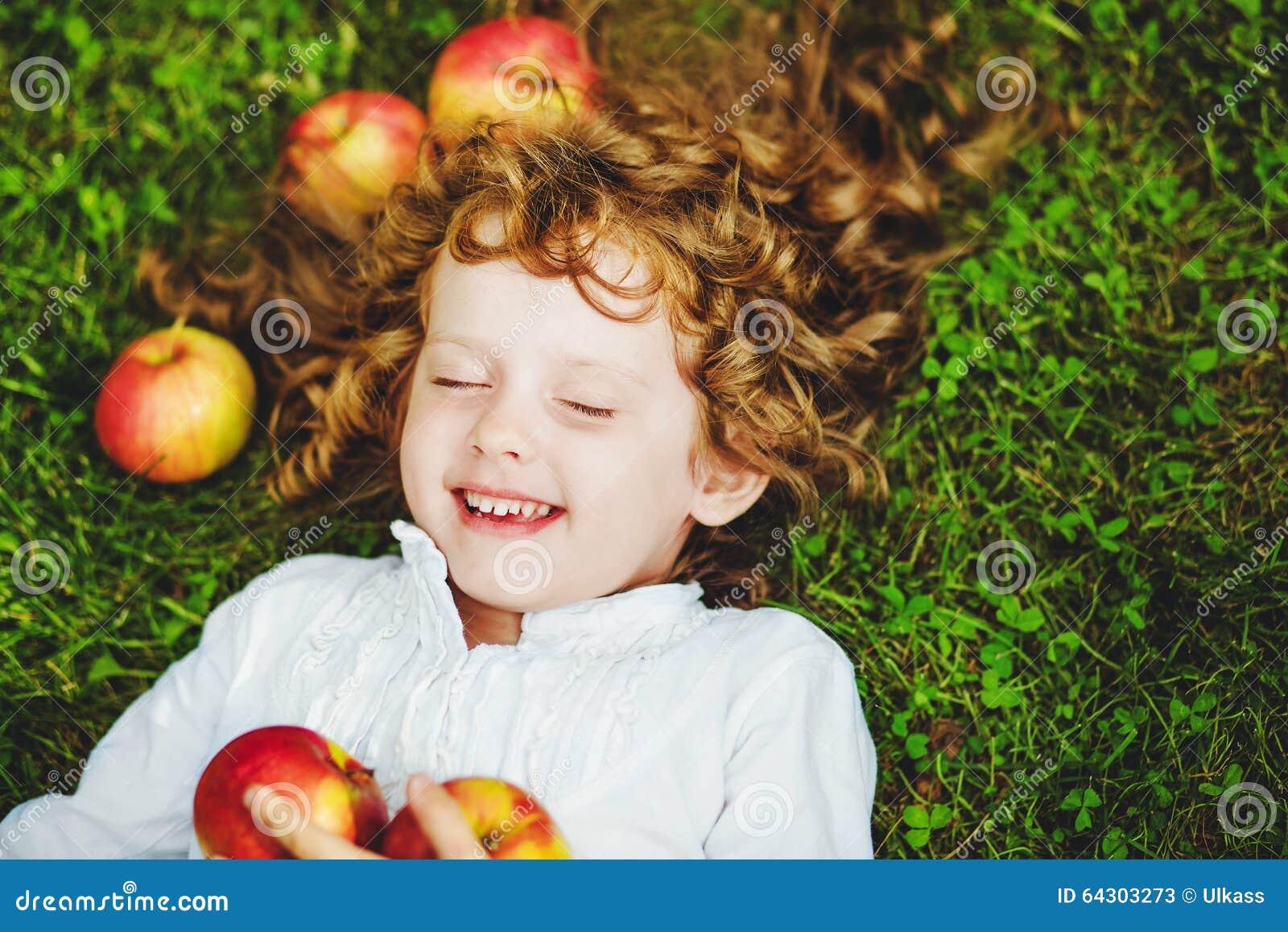 Το σγουρό κορίτσι βρίσκεται στη χλόη με το μήλο και το χαμόγελο