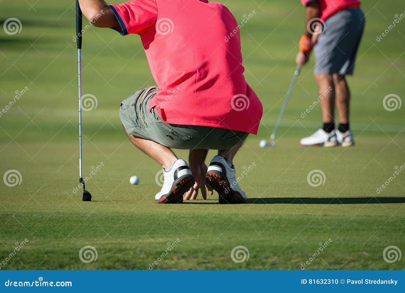 Το σκύψιμο φορέων γκολφ και μελετά το πράσινο πρίν βάζει τον πυροβολισμό