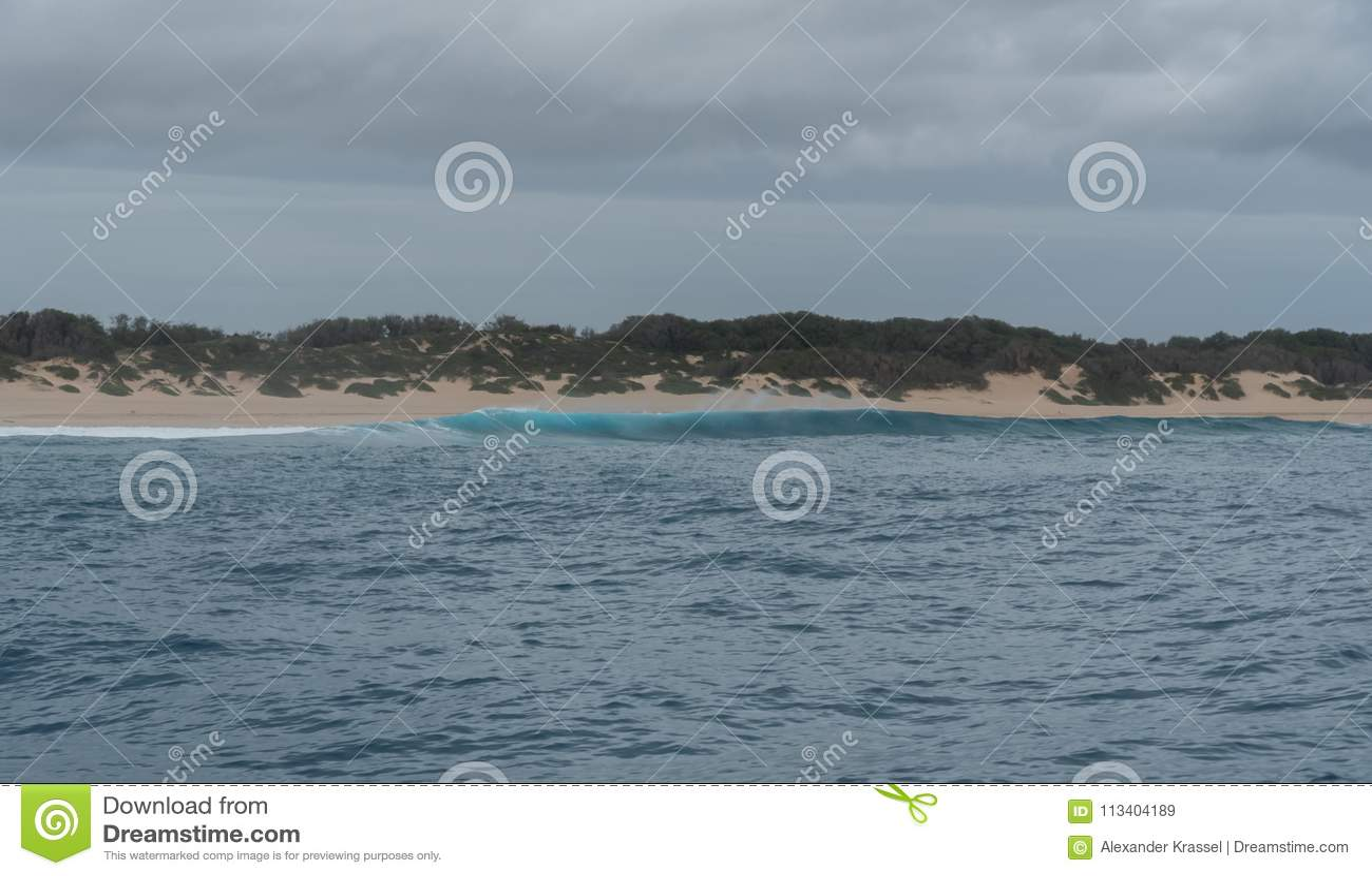 Το σπάσιμο κυμάτων στην αποφλοίωση στρώνει με άμμο την παραλία στη δυτική ακτή Kauai, Χαβάη, το χειμώνα