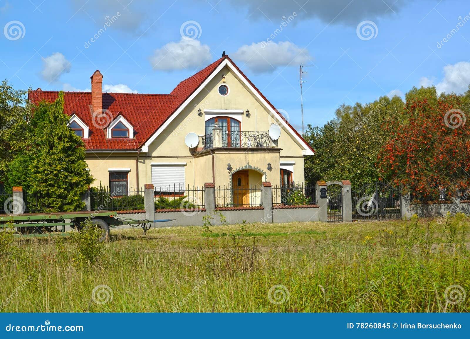Το σπίτι διαμερισμάτων χωρών με ένα μπαλκόνι μπλε καλοκαίρι της Ρωσίας στεγών περιοχών σπιτιών ημέρας kaliningrad ηλιόλουστο