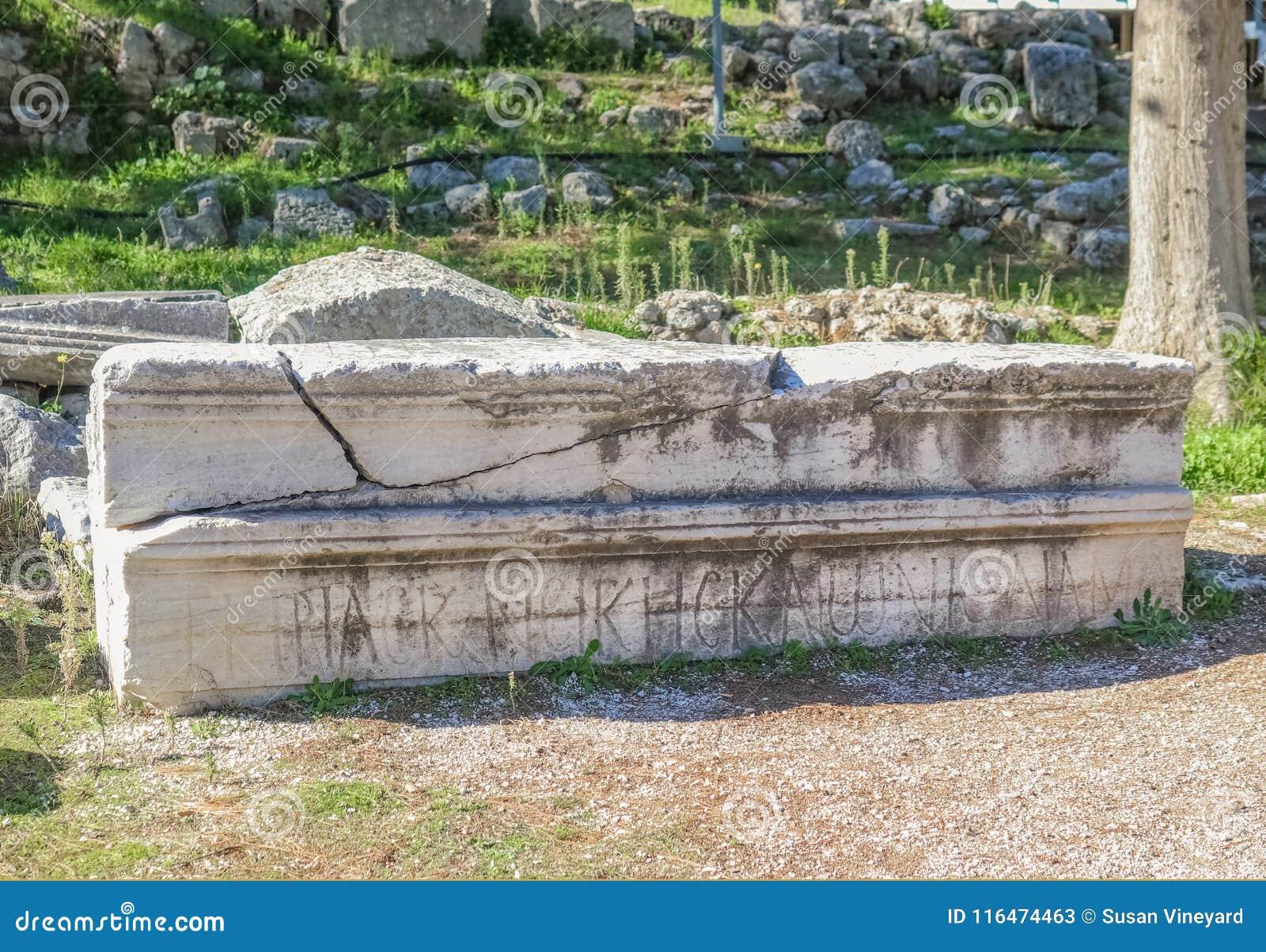 Το σπασμένο μακροχρόνιο μαρμάρινο κομμάτι ενός κτηρίου χάρασε με τις ρωμαϊκές επιστολές που συσσωρεύθηκαν εκτός από τις καταστροφ